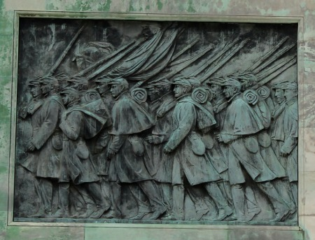 MARCHING SOLDIERS AT BASE OF SCULPTURE